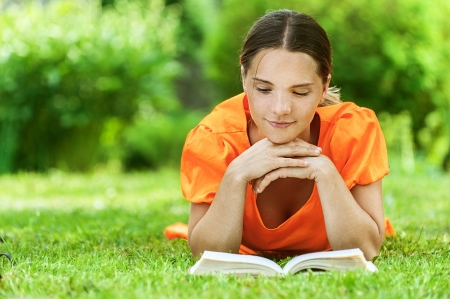 one story: Dark-haired smiling beautiful young woman in orange blouse lying on grass and reading book, against green of summer park.