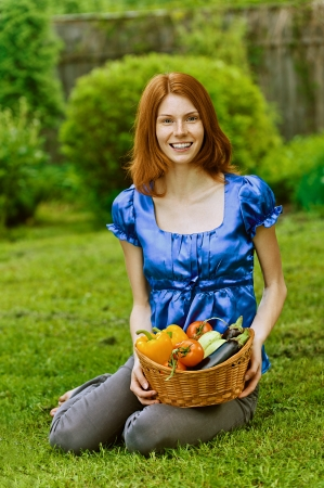 brinjal: Portrait of red-haired smiling beautiful young woman in blue blouse with baskets of fruit and vegetables, against green of summer park. Stock Photo