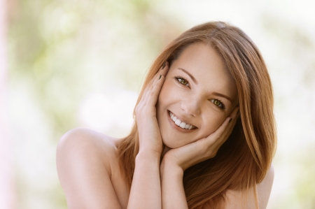 bare shoulders: Portrait of smiling beautiful young woman with bare shoulders close up, against green of summer park.