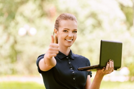 Beautiful smiling young woman in dark blouse keeps your laptop and lifts thumb upwards, against green of summer park. photo