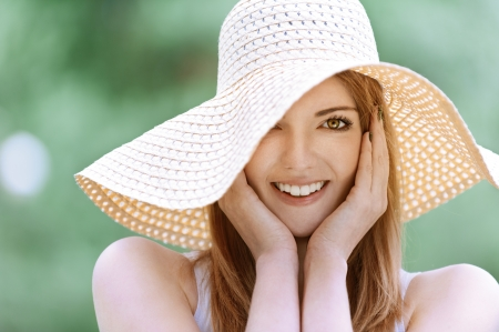 Portrait of smiling beautiful young woman in summer cap closeup, against green of summer park. photo