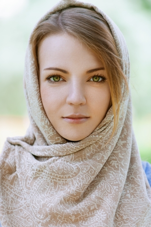headscarf: Portrait of calm beautiful young woman in head scarf close up, against green of summer park. Stock Photo