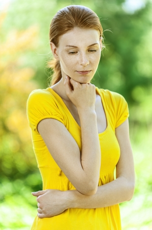 eyes looking down: Portrait of red-haired pensive beautiful young woman in yellow blouse, against green of summer park.