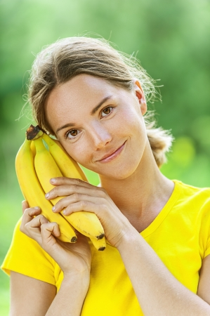 Portrait of dark-haired smiling beautiful young woman in yellow blouse with banana, against green of summer park. photo