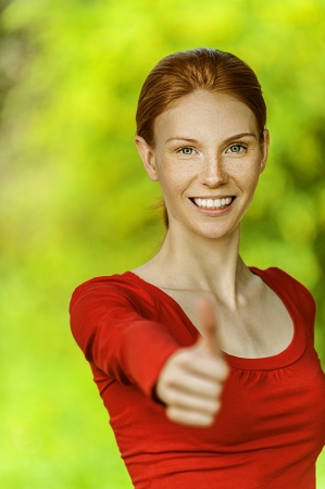 Red-haired smiling beautiful young woman in red blouse lifts thumb upwards, against green of summer park. Stock Photo - 15501951