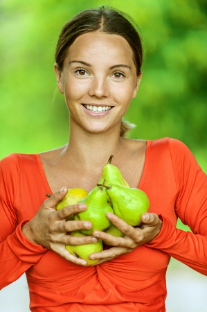 Portrait of dark-haired smiling beautiful young woman in red blouse with pears, against green of summer park. photo