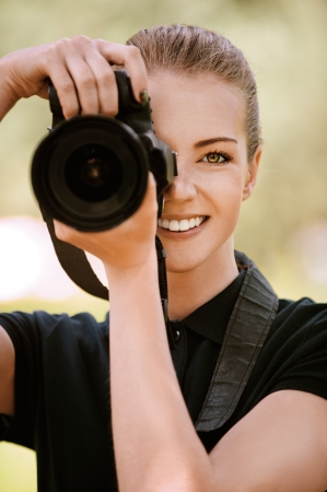 photographers: Beautiful smiling young woman in dark blouse photographs on camera, against green of summer park.