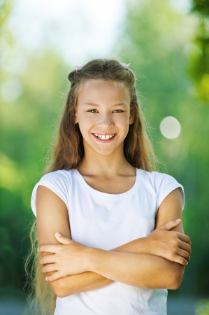adolescence: Beautiful smiling teenage girl in white blouse, against green of summer park.