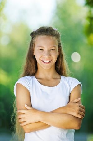 adolescencia: Hermosa adolescente sonriente en la blusa blanca, contra el verde del Parque de verano. Foto de archivo