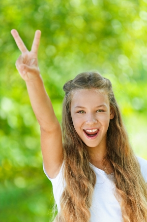 Beautiful teenage girl in white blouse up two fingers in victory sign, against green of summer park. Stock Photo - 15501972