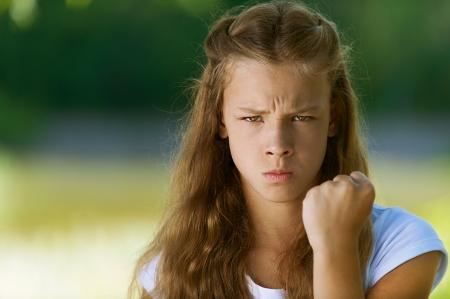 petite fille triste: Belle fille adolescente grave secoue son poing, contre le vert du parc de l'�t�.