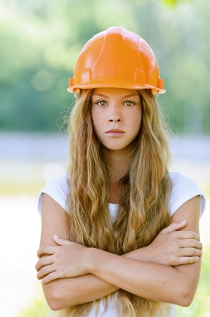 Portrait of beautiful teenage girl in an orange helmet, against green of summer park. Stock Photo - 15501936