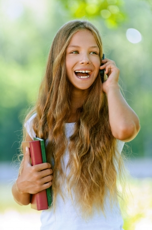 Beautiful laughing teenage girl with books talking on mobile phone, against green of summer park. photo