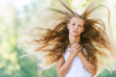 flying hair: Portrait of beautiful teenage wind with flying hair, against green of summer park. Stock Photo