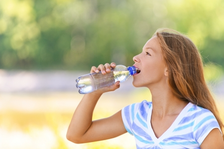 Beautiful teenage girl in blue blouse drinks water from bottle, against green of summer park. Stock Photo - 15501948