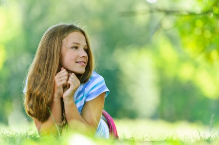 Beautiful smiling teenage girl in blue blouse lying on grass, against green of summer park. Stock Photo - 15501933