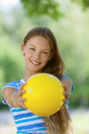 Beautiful smiling teenage girl holding yellow ball, against green of summer park. Stock Photo - 15501950