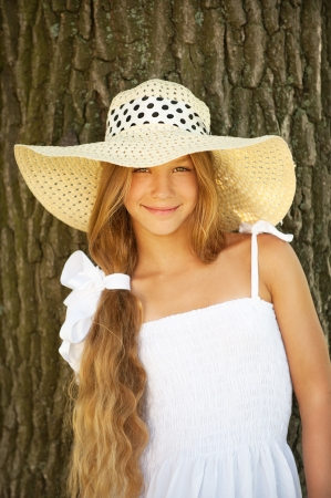 Portrait of smiling beautiful teenage in wide-brimmed hat, against tree trunk. Stock Photo - 15501971
