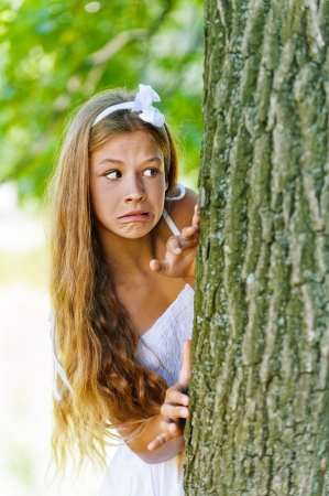 Beautiful frightened teenage peeping from behind tree, against green of summer park. Stock Photo - 15501938