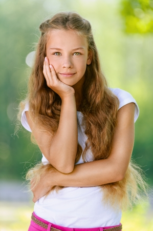 females only: Portrait of beautiful smiling teenage girl in white blouse, against green of summer park.