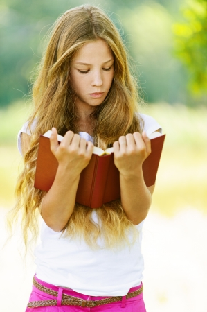 Beautiful teenage girl reading red book, against green of summer park.