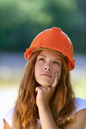 Portrait of beautiful teenage girl in an orange helmet, against green of summer park. Stock Photo - 15282498