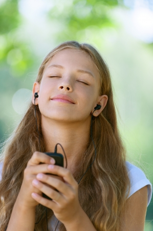 Beautiful teenage girl with headphones listening to music, against green of summer park. photo