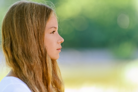 Portrait of beautiful teenage close up profile, against green of summer park. Stock Photo - 15282488