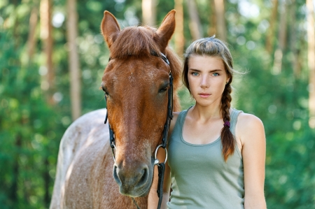 cute young farm girl: Beautiful young woman close-up with horse, against green of summer park. Stock Photo