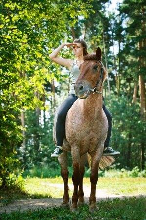 Portrait of beautiful young woman on horseback, against green of summer park. photo