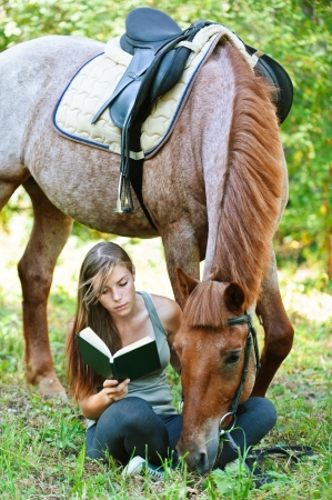 equine: Beautiful young woman reading book with horse, against green of summer park.