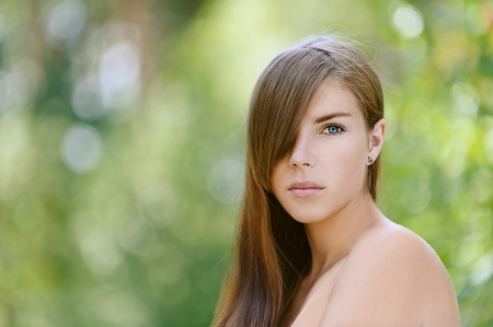 Portrait of beautiful young woman close up, against green of summer park. Stock Photo - 15282487