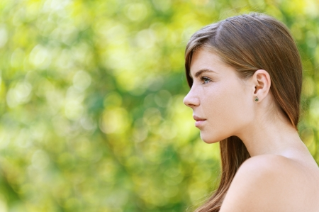 Portrait of beautiful young woman close up in profile, against green of summer park.