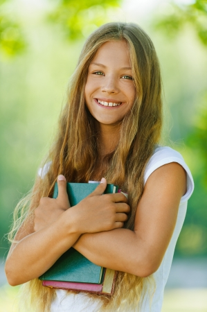 Portrait of smiling beautiful teenage girl with books, against green of summer park.