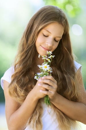 Portrait of smiling beautiful teenage with bouquet of daisies, against green of summer park. Stock Photo - 15365827