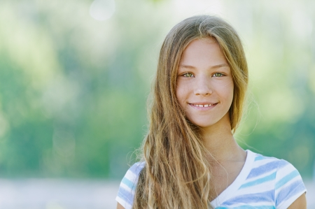 adolescence: Beautiful smiling teenage girl in blue blouse, against green of summer park.