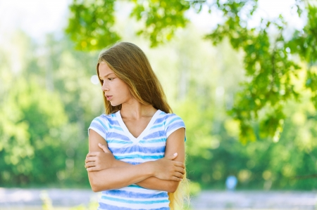 Beautiful sad teenage girl in white blouse, against green of summer park. Stock Photo - 15365822