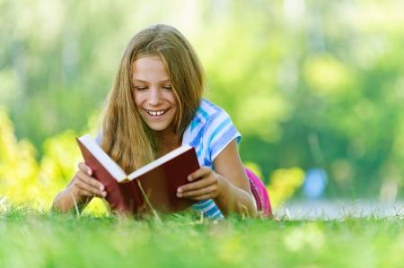 Mooie glimlachende tienermeisje in blauwe blouse liggend op gras en gelezen boek, tegen groen van de zomer park. Stockfoto