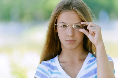 Portrait of beautiful teenage with glasses, against green of summer park. Stock Photo - 15365811