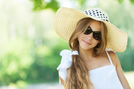 Portrait of smiling beautiful teenage in wide-brimmed hat and sunglasses, against green of summer park. photo