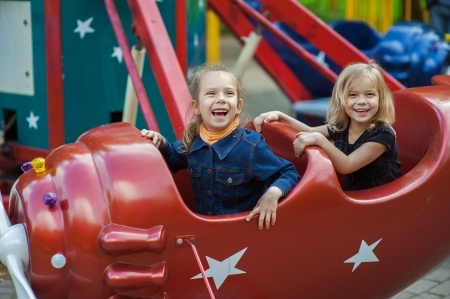 Two funny sisters on carousel ride in red airplane in children Stock Photo - 15530318