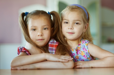 Portrait of two sisters close-up, which sits on table in room Stock Photo - 15530319