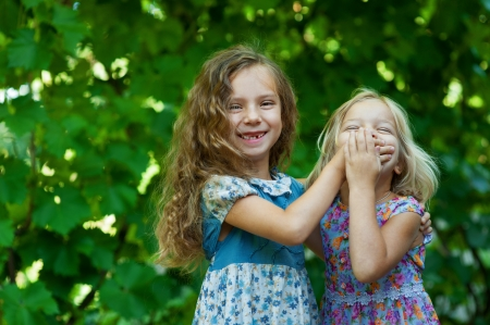 Two sisters playing - with one hand covers mouth of another, against background of summer city park  photo