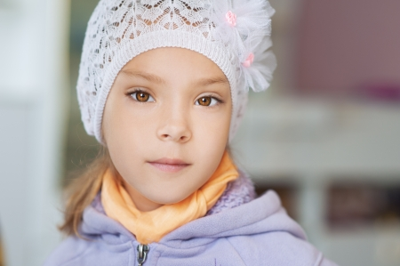 Beautiful little girl in warm jacket and white hat indoors. Stock Photo - 15465026