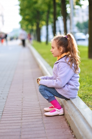 curb: Beautiful little girl in jacket sitting on paving-stone curb profile, against background of city street.