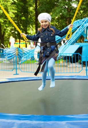 trampoline: Beautiful happy little girl jumping on trampoline, against background of childrens park. Stock Photo