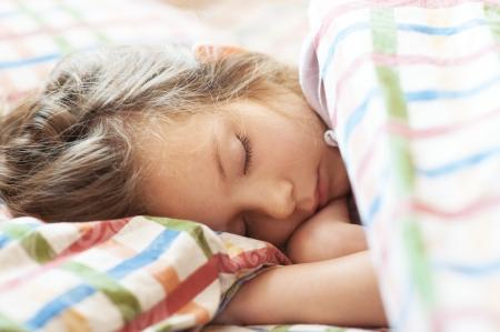 enfant qui dort: Belle petite fille dormir dans le lit de près.