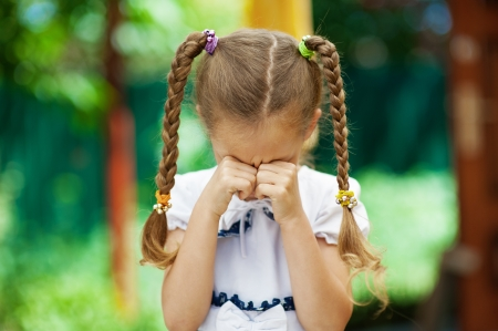 tresses: Beautiful little girl with pigtails crying, against background of summer park.