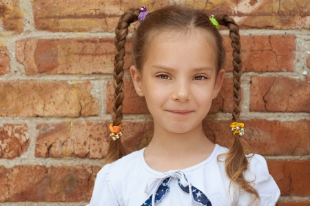 pigtail: Portrait of smiling beautiful little girl close-up, against background of a brick wall. Stock Photo