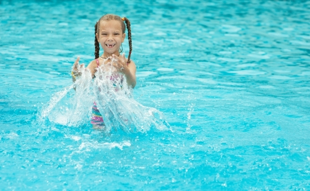 Portrait of beautiful smiling little girl at resort in warm comfortable pool. photo